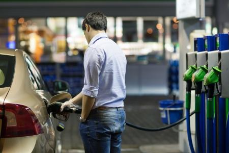 surtidor de gasolina: Joven alimentando su coche en la gasolinera Foto de archivo