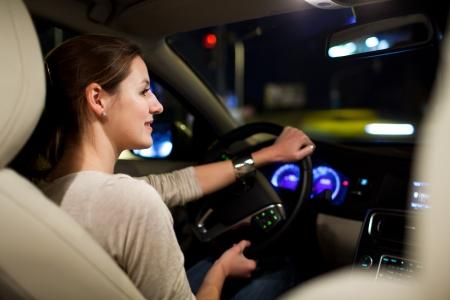Het besturen van een auto 's nachts - mooie, jonge vrouw rijdt haar moderne auto' s nachts in een stad (ondiepe DOF, kleur getinte afbeelding)