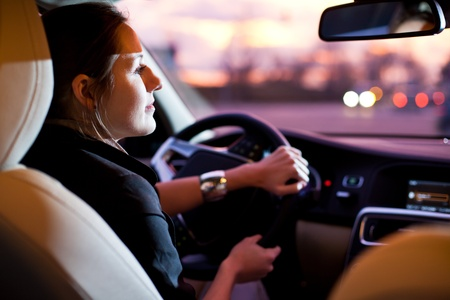 windscreen: Driving a car at night - pretty, young woman driving her modern car at night in a city (shallow DOF; color toned image) Stock Photo