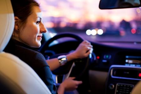 manejando: Conducir un coche por la noche - mujer bonita, joven conduc�a su autom�vil moderno en la noche en una ciudad (DOF bajo; imagen de tonos de color)