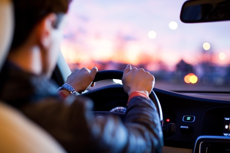 Driving a car at night - pretty, young woman driving her modern car at night in a city (shallow DOF; color toned image) Stock Photo