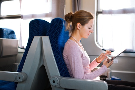 computer user: Young woman using her tablet computer while traveling by train Stock Photo