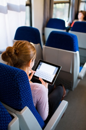 commuter train: Young woman using her tablet computer while traveling by train Stock Photo