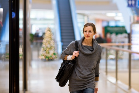 Young woman looking at store windows when shopping in a shopping mallcenter photo