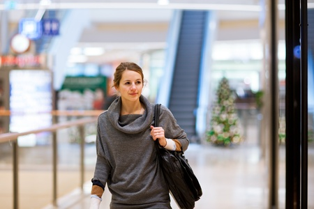 Young woman looking at store windows when shopping in a shopping mall/center Stock Photo - 12405644