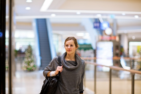 Young woman looking at store windows when shopping in a shopping mall/center Stock Photo - 12405682