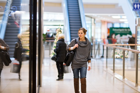 Young woman looking at store windows when shopping in a shopping mall/center Stock Photo - 12405638