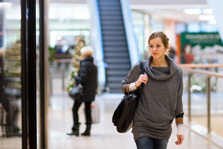 civilisation: Young woman looking at store windows when shopping in a shopping mallcenter