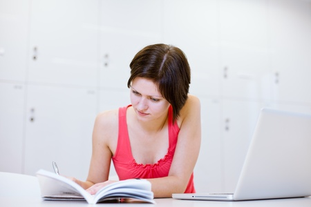 Pretty young college student studying in the librarya study room at campus (color toned image; shallow DOF) photo