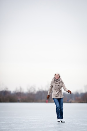 Young woman ice skating outdoors on a pond on a freezing winter day Stock Photo - 12405814