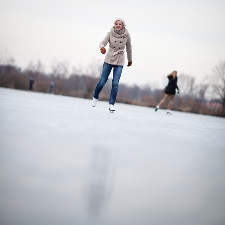 Young woman ice skating outdoors on a pond on a freezing winter day Stock Photo - 12405840