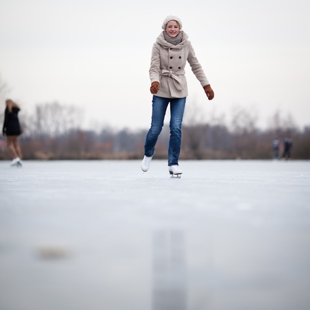speed skating: Young woman ice skating outdoors on a pond on a freezing winter day Stock Photo