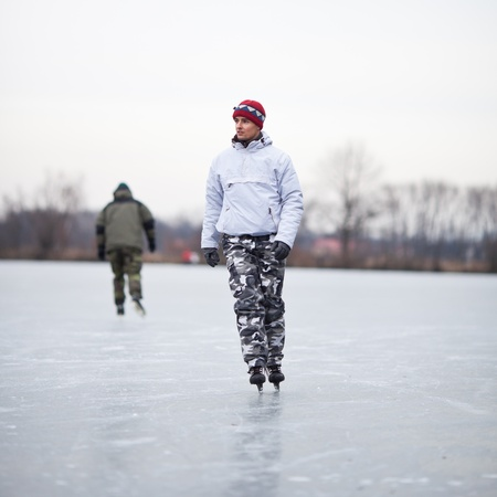 frozen lake: Handsome young man ice skating outdoors on a pond on a cloudy winter day (color toned image; shallow DOF)