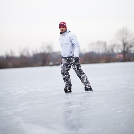 patinaje sobre hielo: Apuesto joven hombre de patinaje sobre hielo al aire libre en un estanque en un día nublado de invierno (imagen a color entonado, DOF bajo)