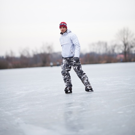 ice skating: Handsome young man ice skating outdoors on a pond on a cloudy winter day (color toned image; shallow DOF)