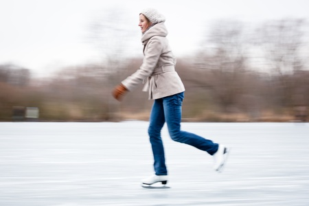 frozen lake: Young woman ice skating outdoors on a pond on a freezing winter day Stock Photo