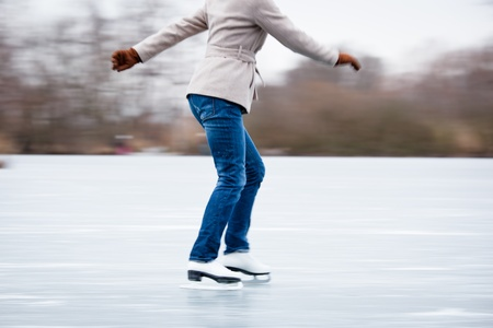 shallow focus: Young woman ice skating outdoors on a pond on a freezing winter day Stock Photo