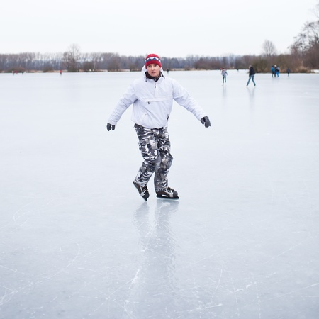 Handsome young man ice skating outdoors on a pond on a cloudy winter day (color toned image; shallow DOF) photo