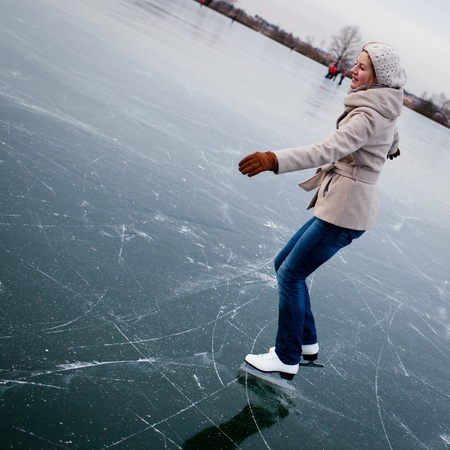 Young woman ice skating outdoors on a pond on a freezing winter day photo