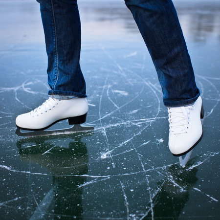 ice skates: Young woman ice skating outdoors on a pond on a freezing winter day Stock Photo