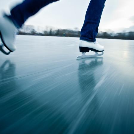 schaatsen: Jonge vrouw schaatsen buiten op een vijver op een ijskoude winterdag
