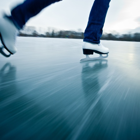 patinaje sobre hielo: Mujer joven de patinaje sobre hielo al aire libre en un estanque en un día helado de invierno