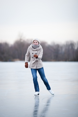 Young woman ice skating outdoors on a pond on a freezing winter day Stock Photo - 12405846
