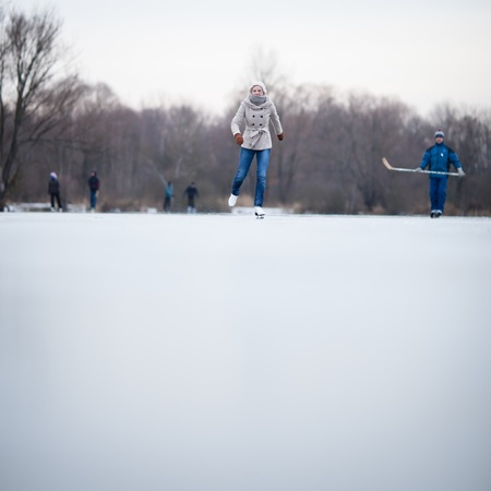 Young woman ice skating outdoors on a pond on a freezing winter day Stock Photo - 12405820
