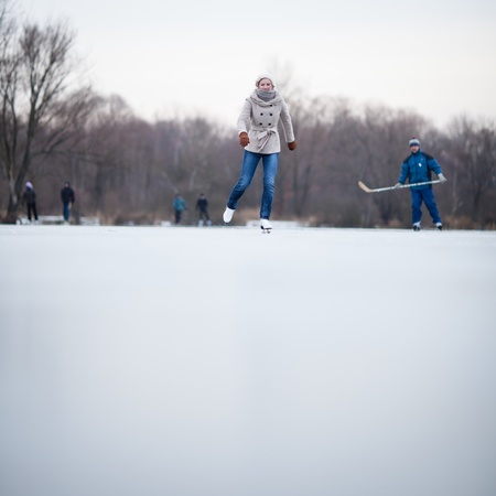 Young woman ice skating outdoors on a pond on a freezing winter day Stock Photo - 12405839