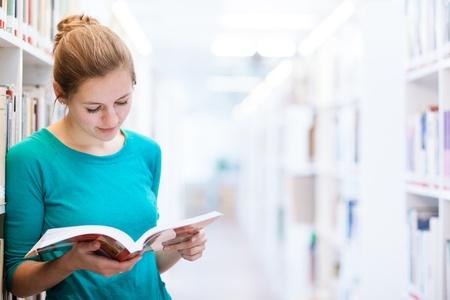 biblioteca: estudiante universitaria en una biblioteca (DOF bajo; imagen de tonos de color) Foto de archivo