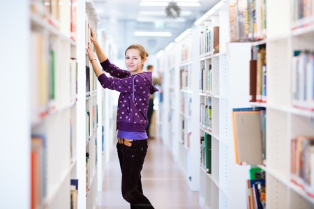college campus: female college student in a library (shallow DOF; color toned image) Stock Photo