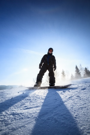 Young man snowboarding down a slope on a lovely sunny winter day photo