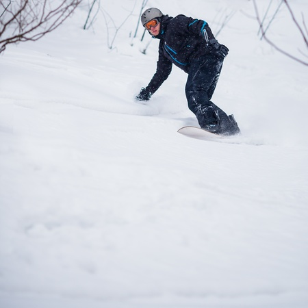 offpiste: Young man freeride snowboarding off-piste in a mountain resort  on a snowy winter day Stock Photo