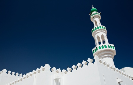 White mosque with minaret against blue sky (Sur, Oman)