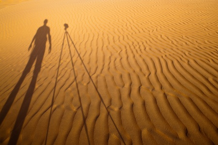 Shadow of a photographer standing next to his tripod cast on dunes of sand in a desert photo