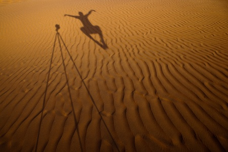 Shadow of a photographer levitating next to his tripod cast on dunes of sand in a desert photo
