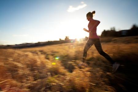 Mujer joven correr al aire libre en una bonita y soleada de invierno / otoño día (movimiento de la imagen borrosa)
