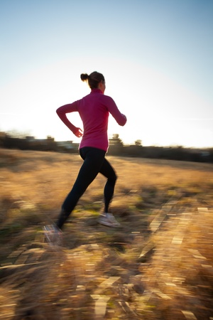 Young woman running outdoors on a lovely sunny winterfall day (motion blurred image) photo