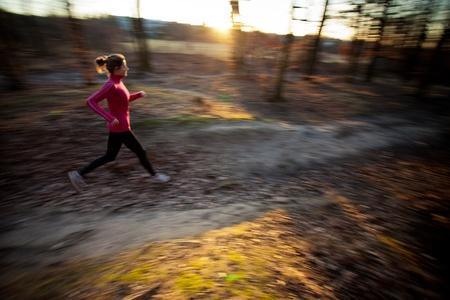 mujeres corriendo: Mujer joven correr al aire libre en un parque de la ciudad en una fr�a de oto�o  invierno d�a (movimiento de la imagen borrosa)