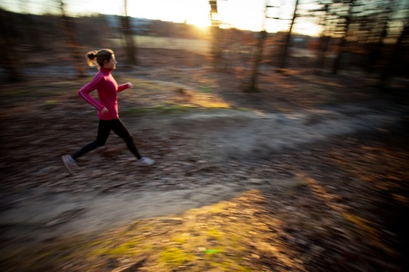 Young woman running outdoors in a city park on a cold fall/winter day (motion blurred image) Stock Photo - 12406342