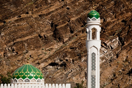 oman background: White mosque with minaret against rocky background (Muscat, Oman) Stock Photo