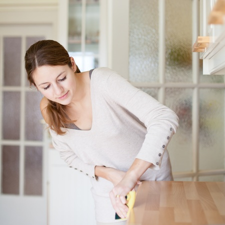 Young woman doing housework, cleaning the kitchen photo