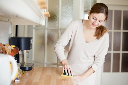 household tasks: Young woman doing housework, cleaning the kitchen Stock Photo