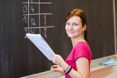 pretty young college student by the chalkboardblackboard during a math class (color toned image) photo