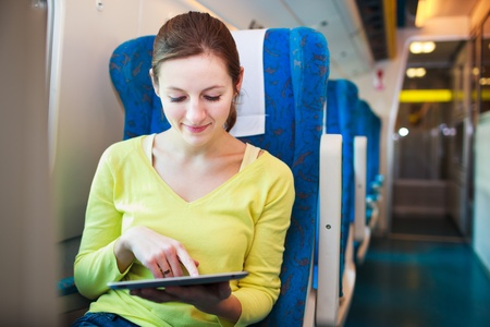 Young woman using her tablet computer while traveling by train Stock Photo