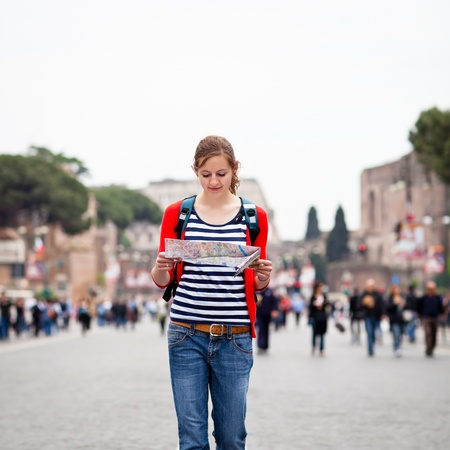 tour guide: Turista femenino bastante joven sosteniendo un mapa mientras se camina a lo largo de la Via del Fori Imperiali avenida de Roma, Italia, con el Coliseo de fondo