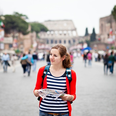 Pretty young female tourist holding a map while walking along the Via del Fori Imperiali avenue in Rome, Italy  with Colosseum in the background  photo