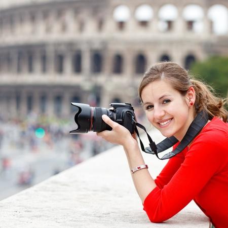 Retrato de una joven turista bastante tomar fotografías al mismo tiempo hacer turismo en Roma, Italia, con el Coliseo en el fondo