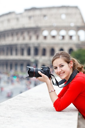 Portrait of a pretty young tourist taking photographs while sightseeing in Rome, Italy (with Colosseum in the background) photo