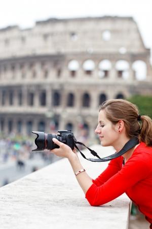 Retrato de una joven turista bastante tomar fotografías al mismo tiempo hacer turismo en Roma, Italia (con el Coliseo al fondo)